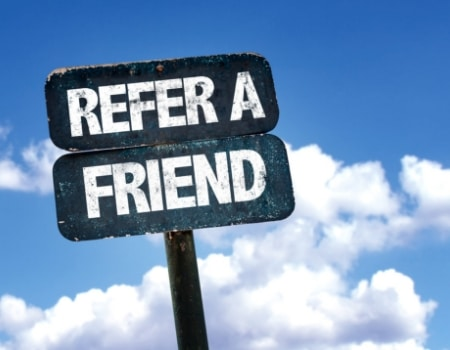 """A black sign reading, """"refer a friend,"""" in front of a blue sky."""