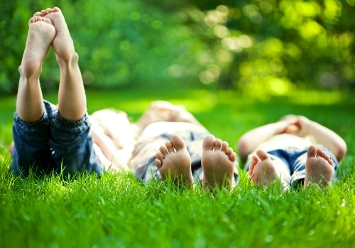 Three young children laying in the grass together.